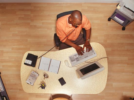 Birds eye view of an employee working at computer in office