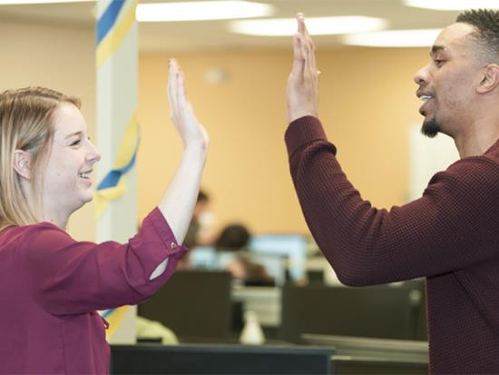Two employees giving a high-five