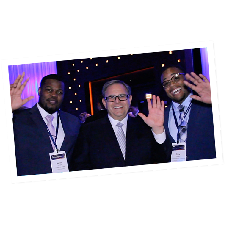 Three men waving at the camera during the leadership conference