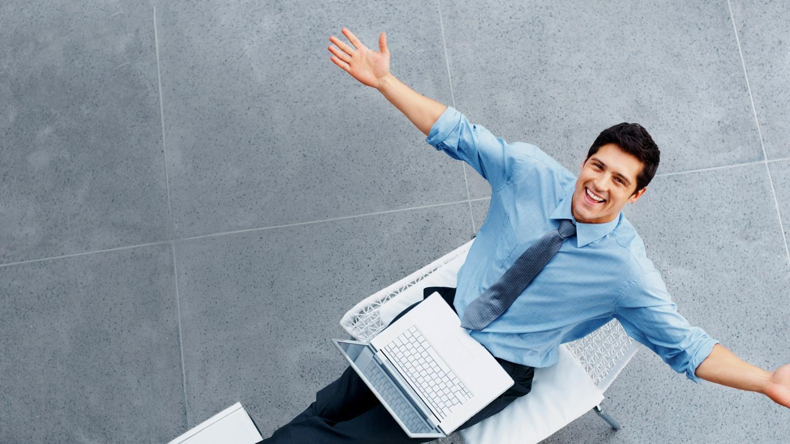 Male Employee sat at Laptop with arms outstretched (1)