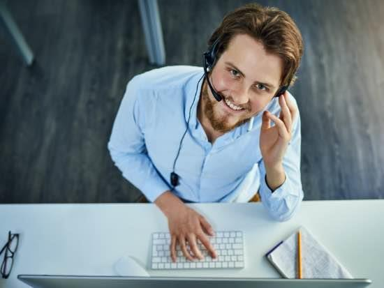 Sales team member working at computer wearing headset